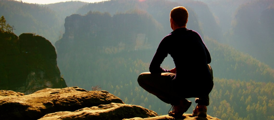 Hiker in black on rocky summit. Wonderful daybreak in mountains, heavy orange mist in deep valley. Man sit on the rock.