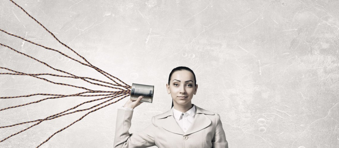 Young businesswoman using tin can and string as communication tool